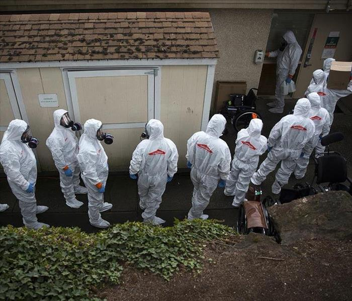 1. Servpro team entering building all in full body suits ready to handle virus