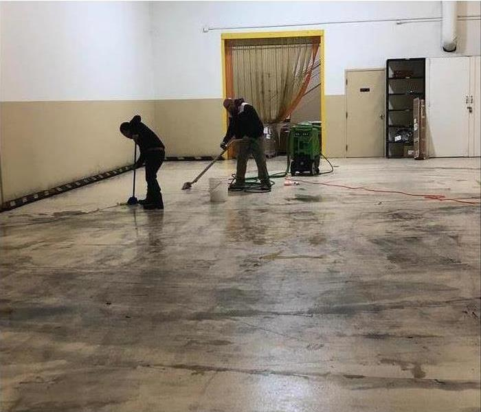 An empty warehouse with SERVPRO employees cleaning all the floors.