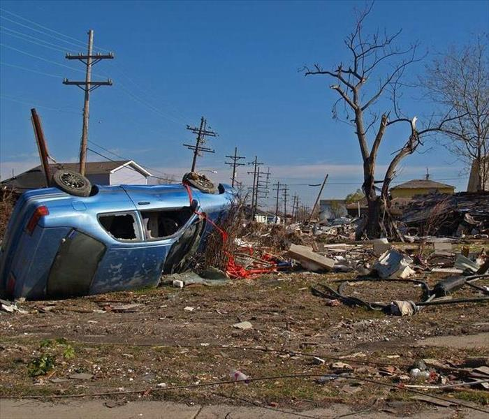 A car lies overturned among storm debris.