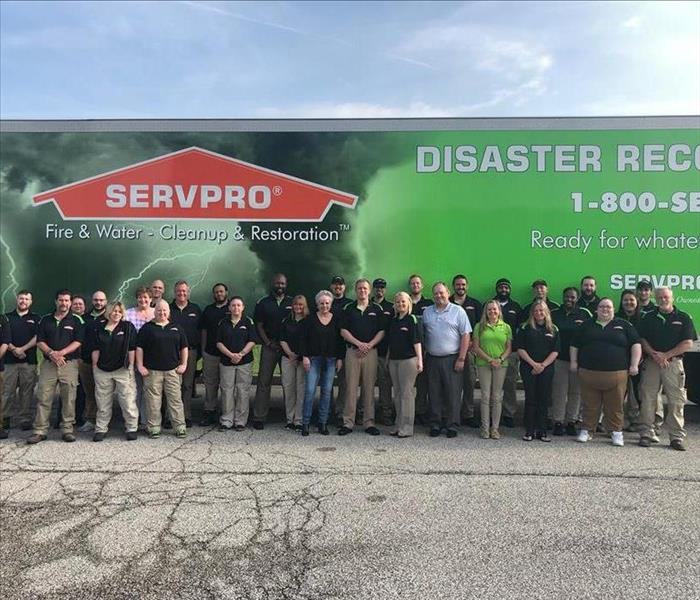 SERVPRO workers stand in front of a SERVPRO truck