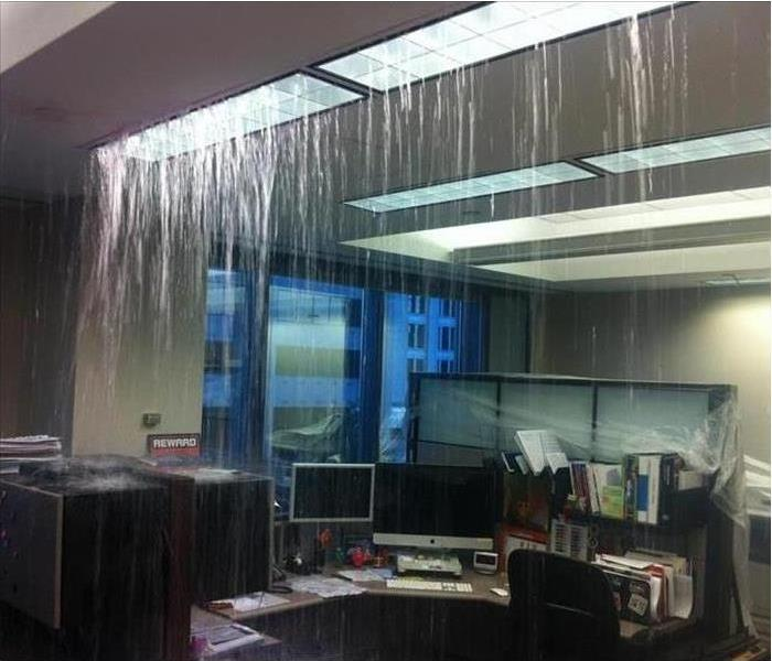 Water pours from a ceiling light fixture in an office