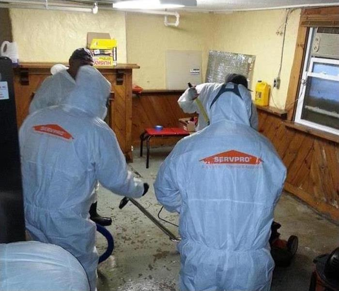 Workers in hazmat suits clean a biohazard-contaminated workplace.