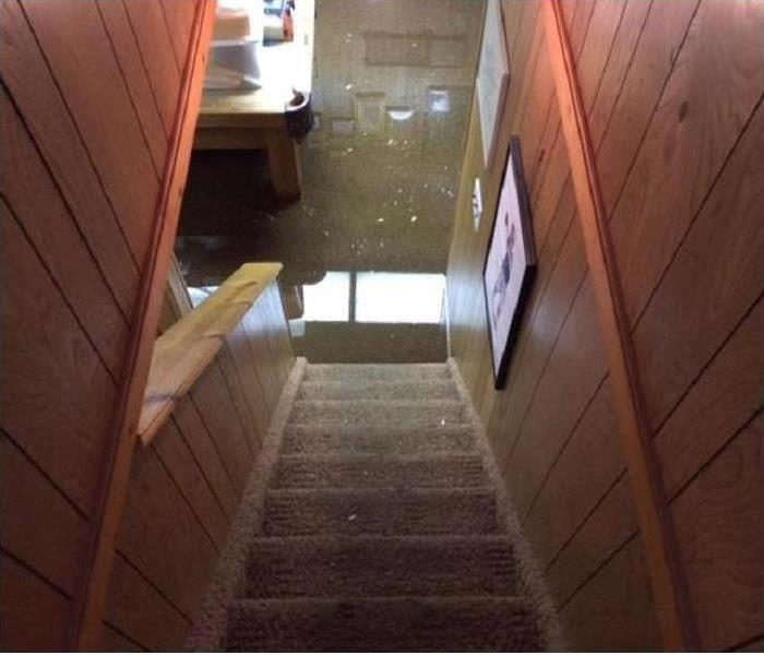 A view down a set of stairs to a flooded basement